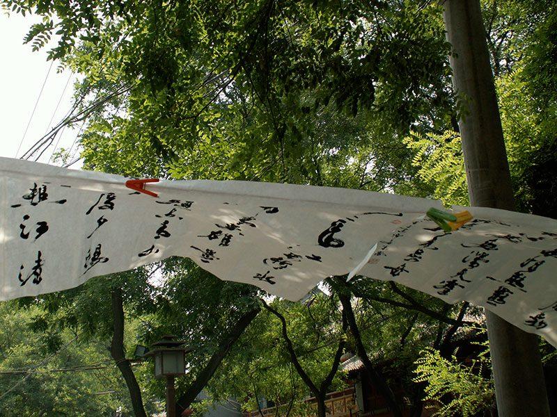Un calligraphe vend ses œuvres dans la rue, galerie improvisée.